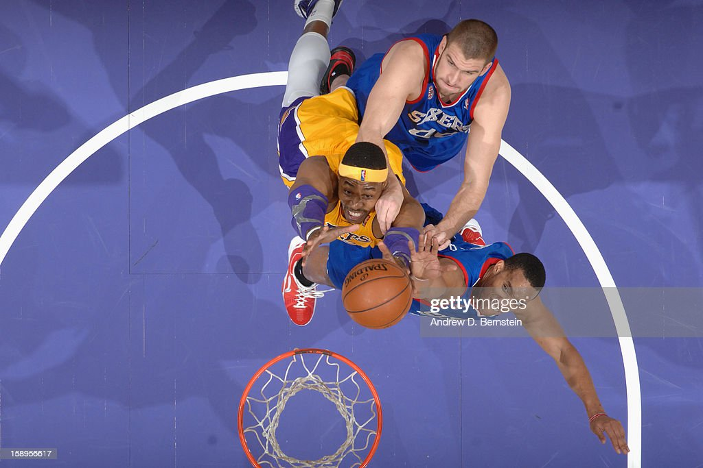 Dwight Howard #12 of the Los Angeles Lakers fights for the rebound against Spencer Hawes #00 and Evan Turner #12 of the Philadelphia 76ers at Staples Center on January 1, 2013 in Los Angeles, California.