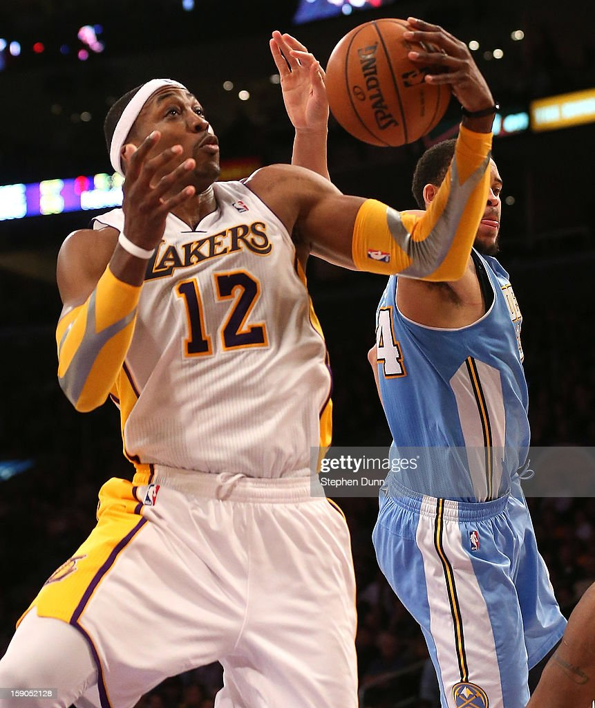 Dwight Howard #12 of the Los Angeles Lakers grabs one of his 26 rebounds in the game, against JaVale McGee #34 of the Denver Nuggets at Staples Center on January 6, 2013 in Los Angeles, California. The Nuggets won 112-105.