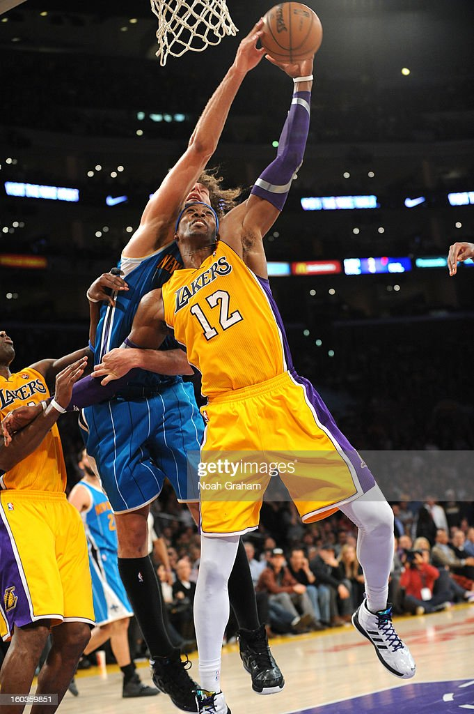 Dwight Howard #12 of the Los Angeles Lakers has his shot blocked by Robin Lopez #15 of the New Orleans Hornets at Staples Center on January 29, 2013 in Los Angeles, California.