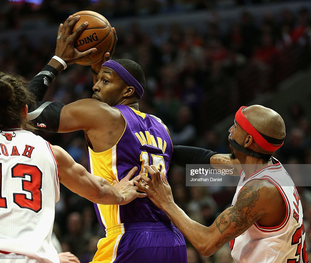 Dwight Howard #12 of the Los Angeles Lakers looks to pass between Joakim Noah #13 and Richard Hamilton #32 of the Chicago Bulls at the United Center on January 21, 2013 in Chicago, Illinois. The Bulls defeated the Lakers 95-83.