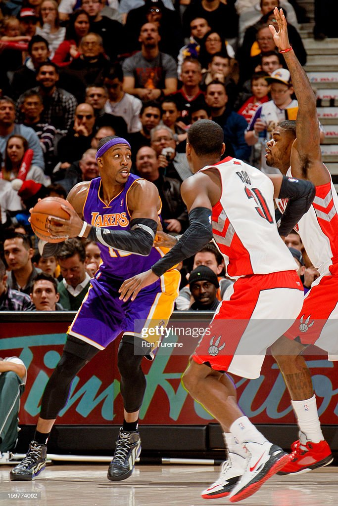 <a gi-track='captionPersonalityLinkClicked' href=/galleries/search?phrase=Dwight+Howard&family=editorial&specificpeople=201570 ng-click='$event.stopPropagation()'>Dwight Howard</a> #12 of the Los Angeles Lakers looks to pass the ball against <a gi-track='captionPersonalityLinkClicked' href=/galleries/search?phrase=Terrence+Ross&family=editorial&specificpeople=6781663 ng-click='$event.stopPropagation()'>Terrence Ross</a> #31 and <a gi-track='captionPersonalityLinkClicked' href=/galleries/search?phrase=Amir+Johnson&family=editorial&specificpeople=556786 ng-click='$event.stopPropagation()'>Amir Johnson</a> #15 of the Toronto Raptors on January 20, 2013 at the Air Canada Centre in Toronto, Ontario, Canada.