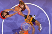 Dwight Howard of the Los Angeles Lakers reaches for a rebound against Alan Anderson and Aaron Gray of the Toronto Raptors at Staples Center on March...