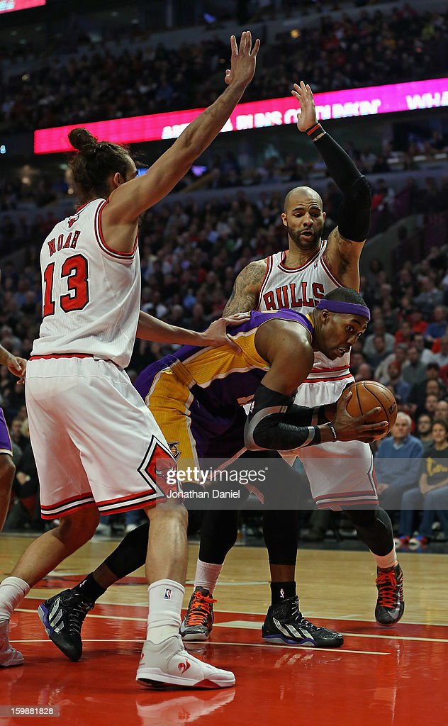Dwight Howard #12 of the Los Angeles Lakers tries to move between Joakim Noah #13 and Carlos Boozer #5of the Chicago Bulls at the United Center on January 21, 2013 in Chicago, Illinois. The Bulls defeated the Lakers 95-83.