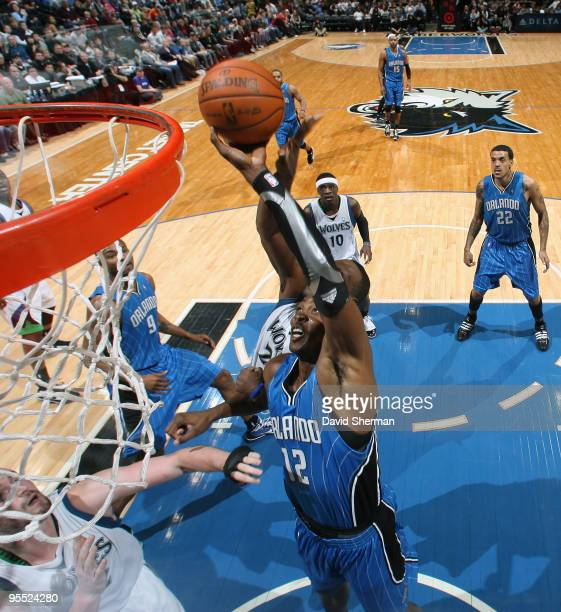 Dwight Howard of the Orlando Magic fights for the rebound against Al Jefferson and Kevin Love of the Minnesota Timberwolves during the game on...