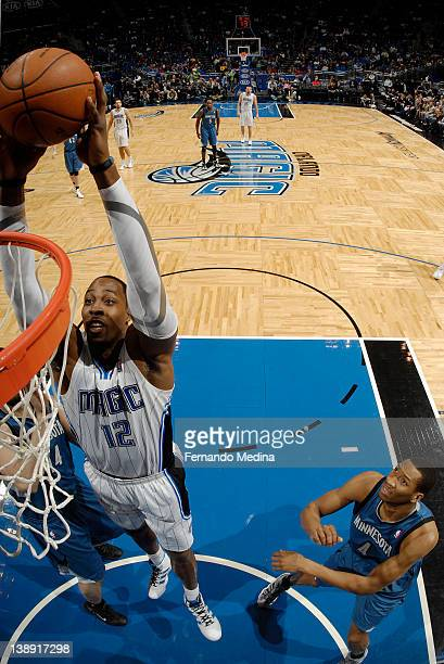 Dwight Howard of the Orlando Magic goes to the basket against Nikola Pekovic of the Minnesota Timberwolves as Wesley Johnson looks on during the game...