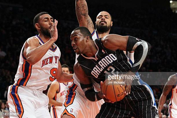 Dwight Howard of the Orlando Magic in action against Tyson Chandler and Jared Jeffries of the New York Knicks on January 16 2012 at Madison Square...