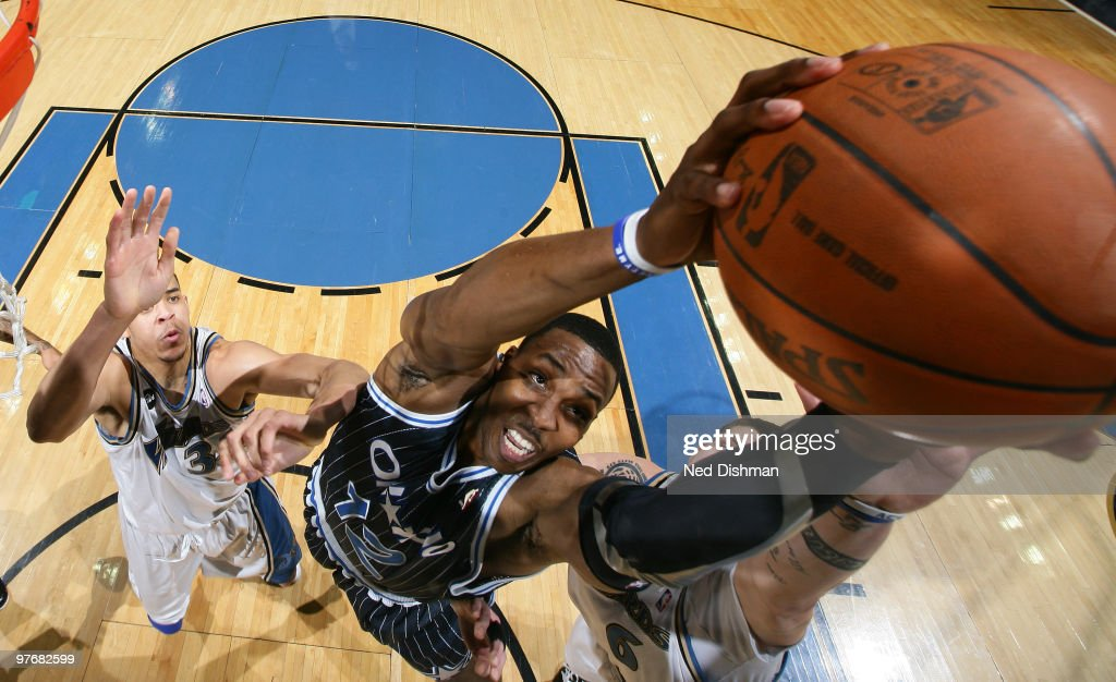 Dwight Howard of the Orlando Magic rebounds against JaVale McGee and Mike Miller of the Washington Wizards at the Verizon Center on March 13 2010 in...