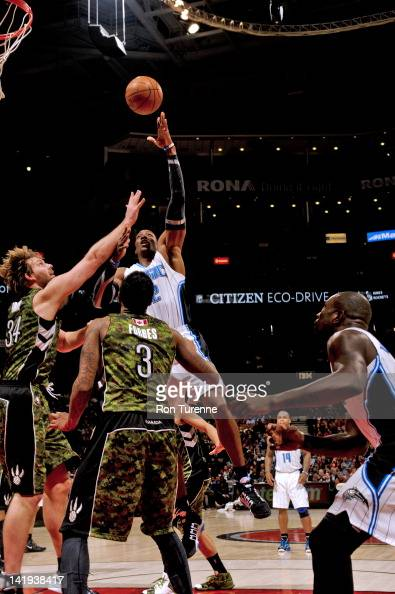 Dwight Howard of the Orlando Magic shoots against Aaron Gray of the Toronto Raptors on March 26 2012 at the Air Canada Centre in Toronto Ontario...