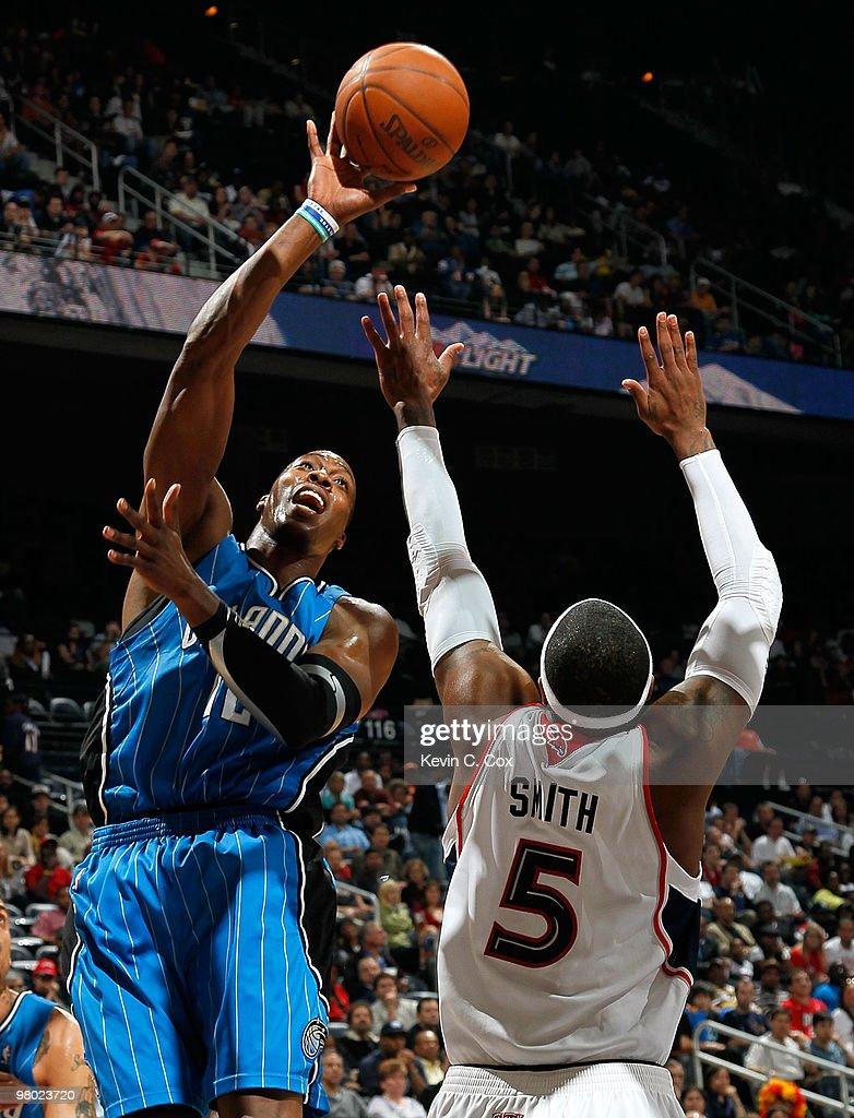 Dwight Howard #12 of the Orlando Magic shoots over Josh Smith #5 of the Atlanta Hawks at Philips Arena on March 24, 2010 in Atlanta, Georgia.
