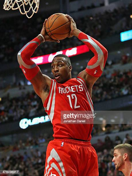 Dwight Howard#12 of the Houston Rockets rebounds against the Chicago Bulls at the United Center on March 13 2014 in Chicago Illinois The Bulls...