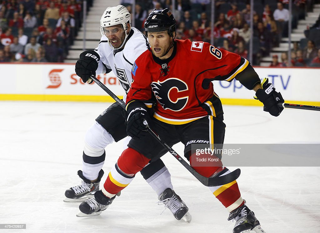 Dwight King (L) of the Los Angeles Kings and Dennis Wideman #6 of the Calgary Flames battle for the puck during the second period of their NHL hockey game at the Scotiabank Saddledome February 27, 2014 in Calgary, Alberta, Canada.
