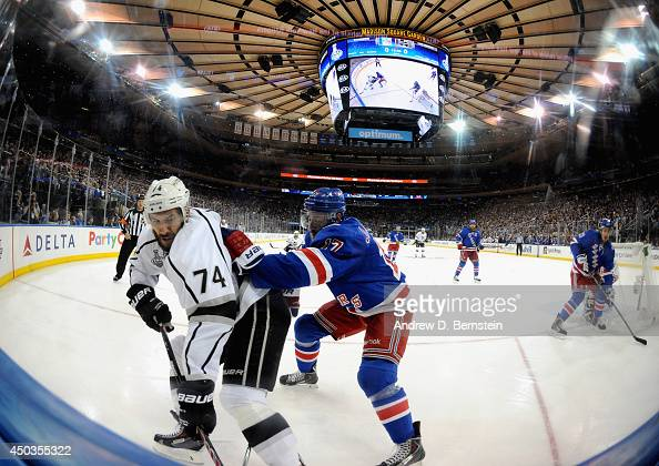 Dwight King of the Los Angeles Kings and John Moore of the New York Rangers play in the first period of Game Three of the 2014 Stanley Cup Final at...