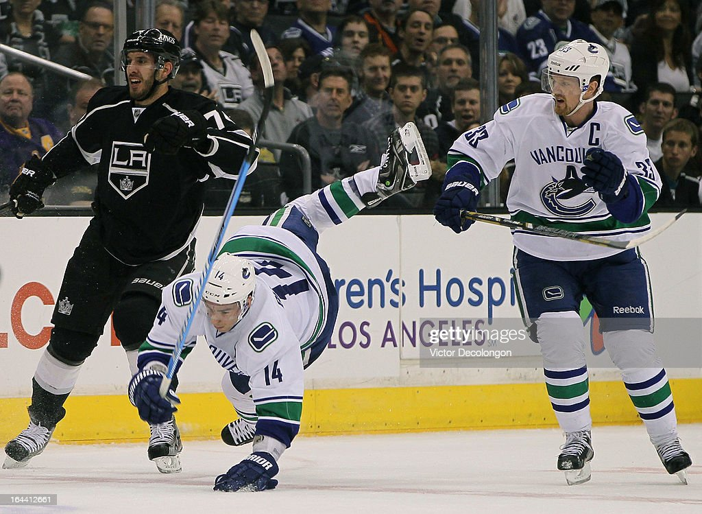 Dwight King #74 of the Los Angeles Kings checks Alex Burrows #14 of the Vancouver Canucks as Henrik Sedin #33 of the Vancouver Canucks looks on in the first period during the NHL game at Staples Center on March 23, 2013 in Los Angeles, California. The Canucks defeated the Kings 1-0.