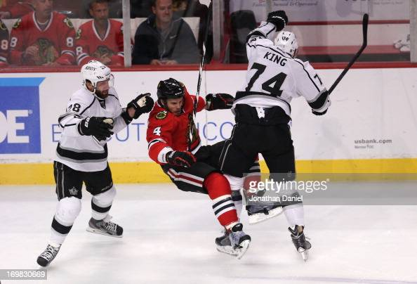 Dwight King of the Los Angeles Kings checks Niklas Hjalmarsson of the Chicago Blackhawks in the neutral zone in the second period of Game Two of the...