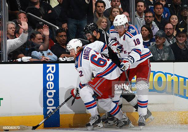 Dwight King of the Los Angeles Kings gets caught at the boards between Carl Hagelin and Marc Staal of the New York Rangers during the third period of...