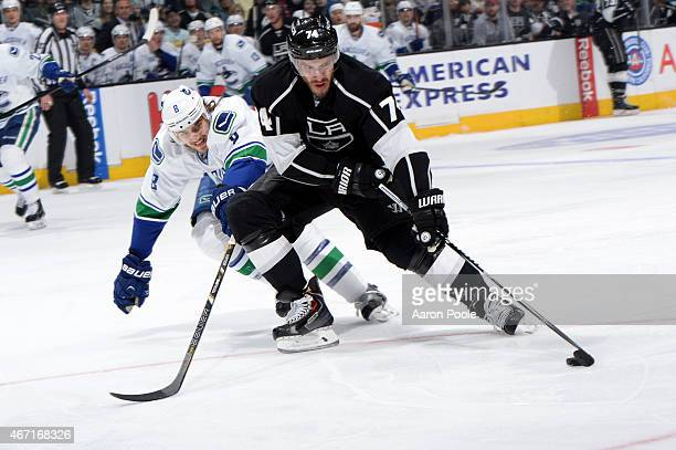 Dwight King of the Los Angeles Kings handles the puck against Chris Tanev of the Vancouver Canucks during a game at STAPLES Center on March 21 2015...