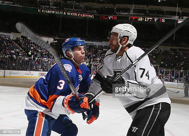 Dwight King of the Los Angeles Kings is checked by Travis Hamonic of the New York Islanders during the first period at the Nassau Veterans Memorial...