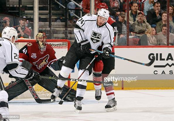 Dwight King of the Los Angeles Kings reacts as he is hit by the puck in front of Michael Stone of the Arizona Coyotes during the second period at...