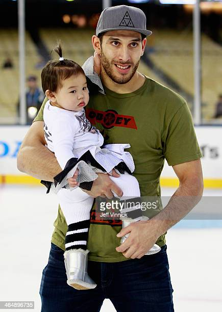 Dwight King of the Los Angeles Kings skates with his daughter Grace prior to the 2014 Coors Light NHL Stadium Series against the Anaheim Ducks at...