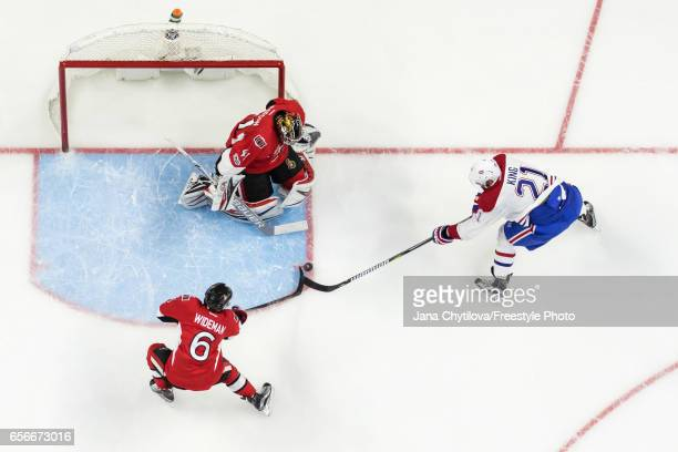 Dwight King of the Montreal Canadiens tries to get his stick on the puck as team mates Craig Anderson and Chris Wideman of the Ottawa Senators defend...
