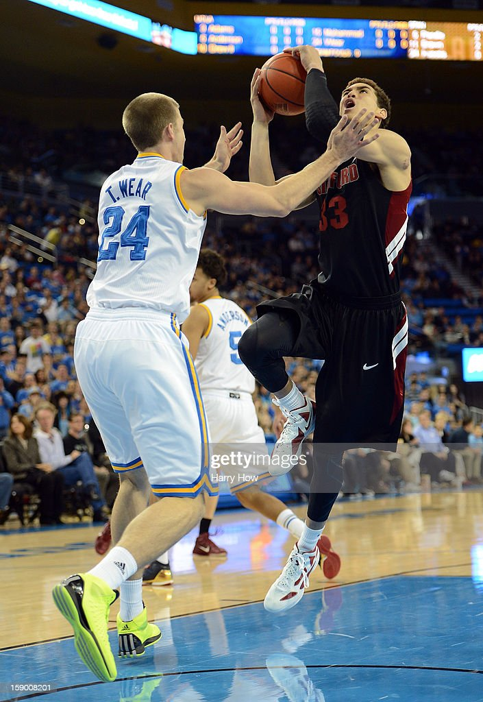Dwight Powell #33 of the Stanford Cardinal drives the lane on Travis Wear #24 of the UCLA Bruins at Pauley Pavilion on January 5, 2013 in Los Angeles, California.