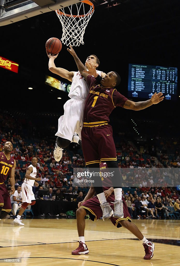 Dwight Powell #33 of the Stanford Cardinal dunks over Jahii Carson #1 of the Arizona State Sun Devils during the first round of the Pac 12 Tournament at the MGM Grand Garden Arena on March 13, 2013 in Las Vegas, Nevada.