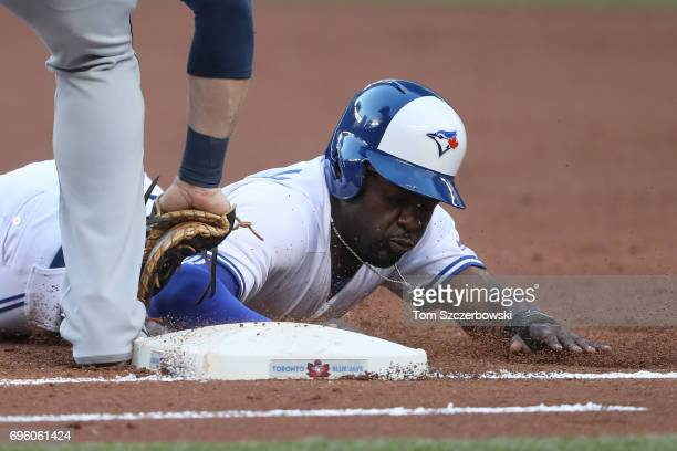 Dwight Smith Jr #15 of the Toronto Blue Jays dives back safely to first base on a pickoff attempt in the second inning during MLB game action against...