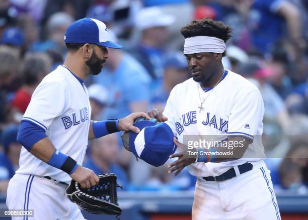 Dwight Smith Jr #15 of the Toronto Blue Jays gets his hat and glove from Jose Bautista after being stranded at the end of the second inning during...