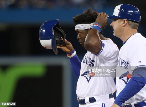 Dwight Smith Jr #15 of the Toronto Blue Jays stands on first base after hitting a single as first base coach Derek Shelton looks on in the eighth...
