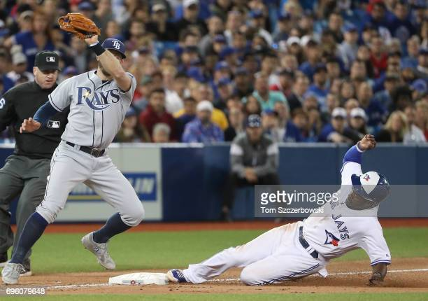 Dwight Smith Jr #15 of the Toronto Blue Jays steals third base in the eighth inning during MLB game action as Evan Longoria of the Tampa Bay Rays...