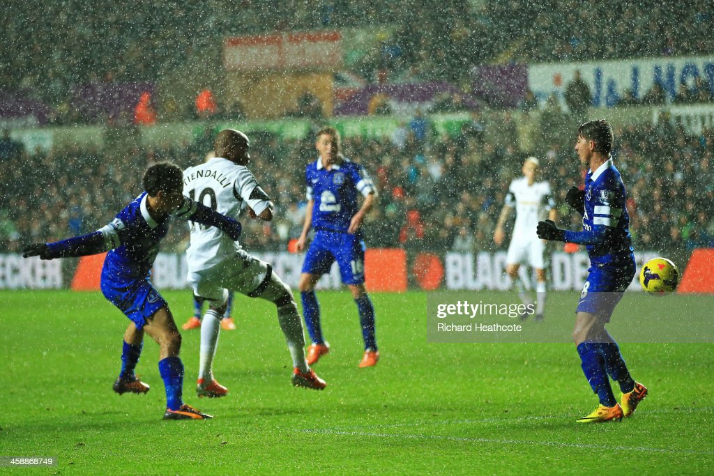 Dwight Tiendalli #10 of Swansea's header on goal is deflected by Bryan Oviedo of Everton #8 (R) for an own goal during the Barclays Premier League match between Swansea City and Everton at the Liberty Stadium on December 22, 2013 in Swansea, Wales.