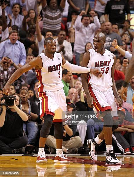 Dwyane Wade and Joel Anthony of the Miami Heat react after Wades dunk during a game against the Oklahoma City Thunder at American Airlines Arena on...