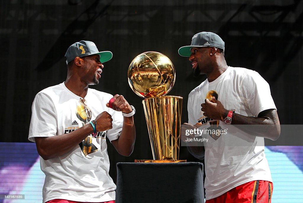 Dwyane Wade #3 and LeBron James #6 of the Miami Heat with the Larry O'Brien trophy during a rally for the 2012 NBA Champions Miami Heat on June 25, 2012 at American Airlines Arena in Miami, Florida.