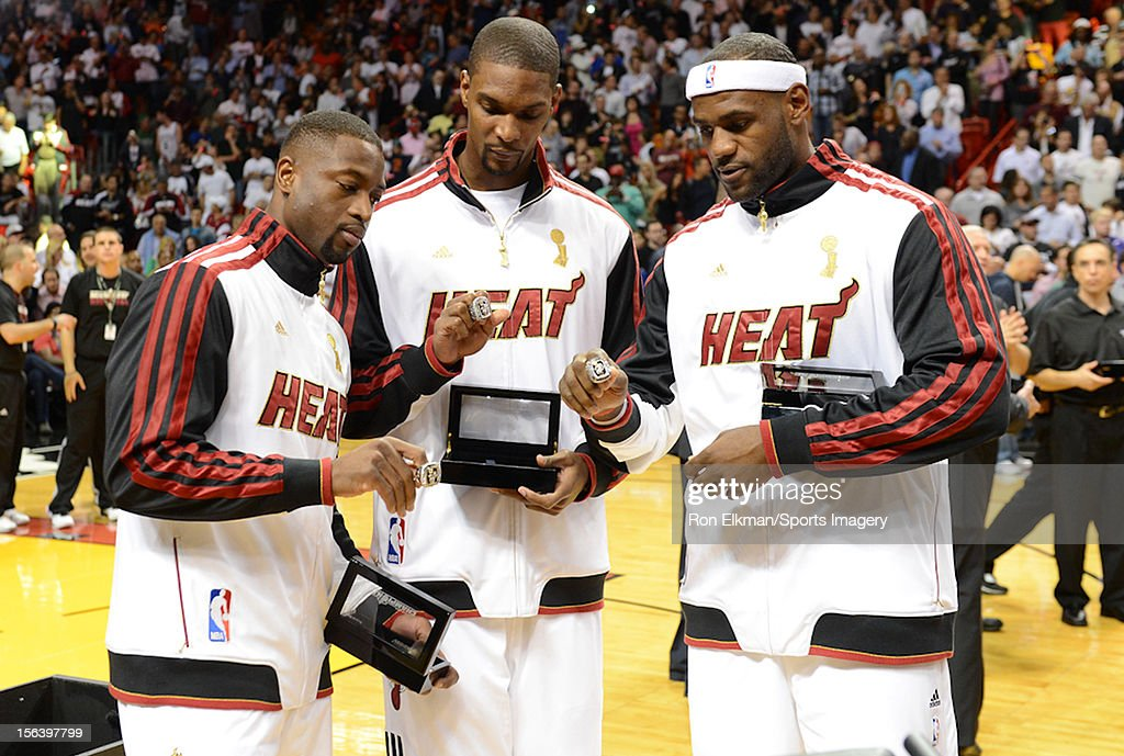 Dwyane Wade #3, Chris Bosh #1 and LeBron James #6 of the Miami Heat pose with their 2012 NBA Championship rings prior to a NBA game against the Boston Celtics at American Airlines Arena on October 30, 2012 in Miami, Florida.