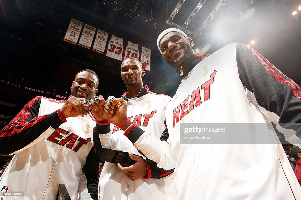Dwyane Wade #3, Chris Bosh #1 and LeBron James #6 of the Miami Heat show off their 2012 NBA Championship rings prior to the NBA game against the Boston Celtics on October 30, 2012 at American Airlines Arena in Miami, Florida.