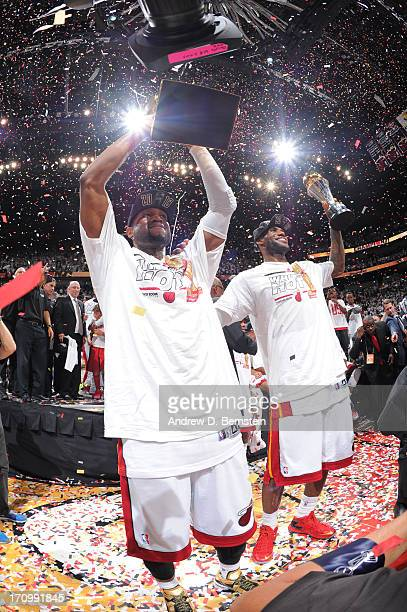 Dwyane Wade holds up the Larry O'Brien Trophy and LeBron James of the Miami Heat holds up the Bill Russell NBA Finals Most Valuable Player Award...