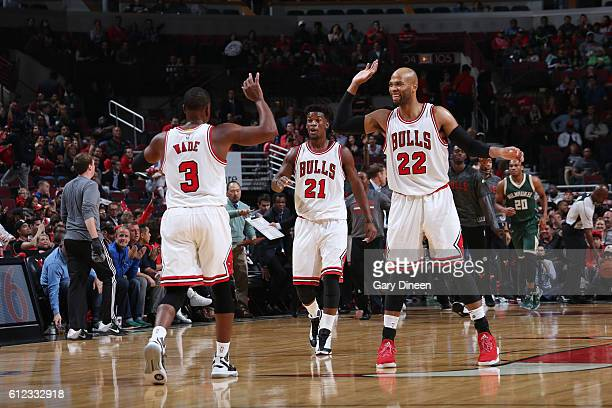 Dwyane Wade Jimmy Butler and Taj Gibson of the Chicago Bulls give high fives drives to the basket against the Milwaukee Bucks during a preseason game...