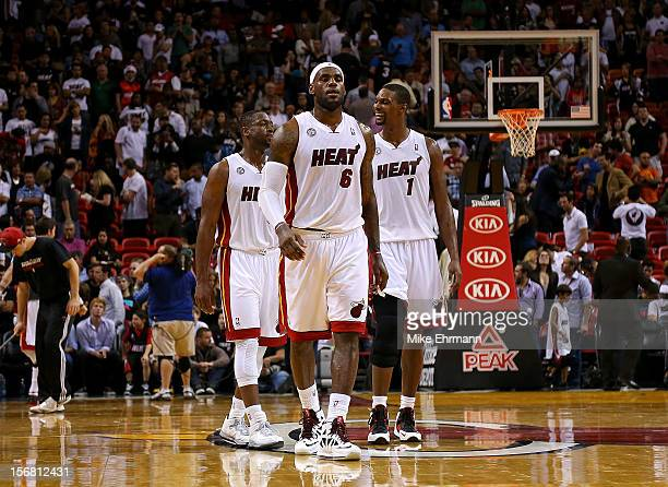 Dwyane Wade LeBron James and Chris Bosh of the Miami Heat look on during a game against the Milwaukee Bucks at AmericanAirlines Arena on November 21...