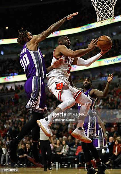 Dwyane Wade of the Chicago Bulls drives past Willie CauleyStein of the Sacramento Kings at the United Center on January 21 2017 in Chicago Illinois...