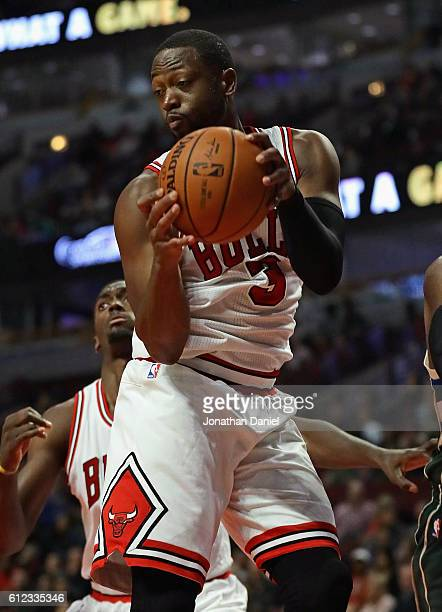 Dwyane Wade of the Chicago Bulls rebounds against the Milwaukee Bucks during a preseason game at the United Center on October 3 2016 in Chicago...