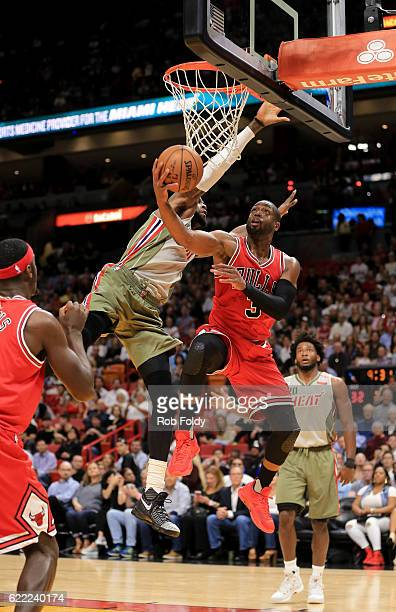 Dwyane Wade of the Chicago Bulls shoots around Willie Reed of the Miami Heat during the first quarter of the game at American Airlines Arena on...