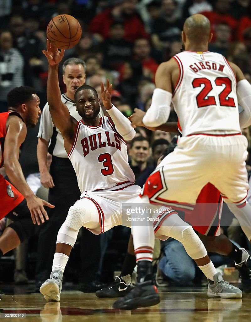 Dwyane Wade #3 of the Chicago Bulls slips as he passes to Taj Gibson #22 against the Portland Trail Blazers at the United Center on December 5, 2016 in Chicago, Illinois.