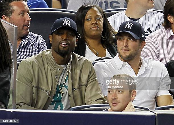 Dwyane Wade of the Miami Heat and Tim Tebow of the New York Jets attend the MLB game between the New York Yankees and the Los Angeles Angels of...