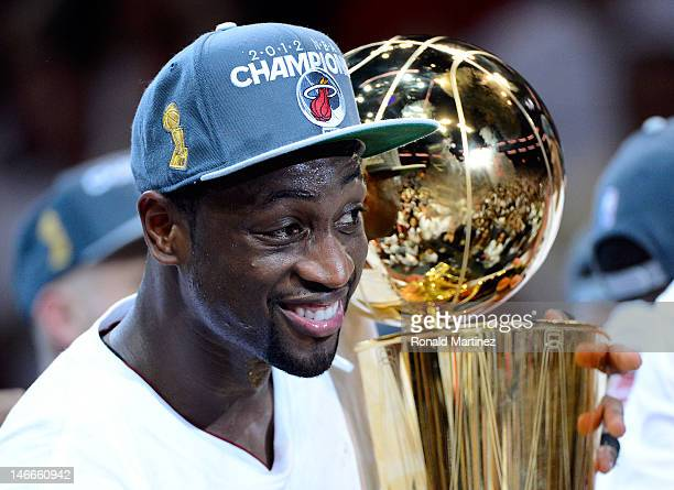 Dwyane Wade of the Miami Heat celebrates with the Larry O'Brien Finals Championship trophy after they won 121106 against the Oklahoma City Thunder in...