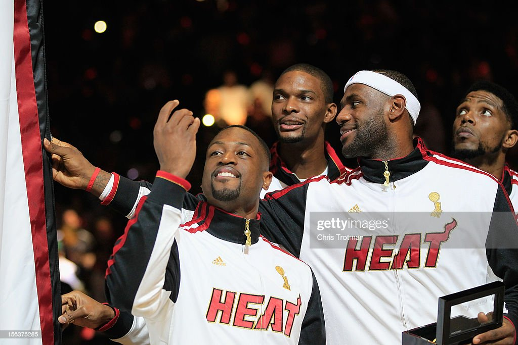 Dwyane Wade #3 of the Miami Heat, (C) Chris Bosh #1 of the Miami Heat and (R) LeBron James #6 of the Miami Heat look at the 2012 NBA Championship banner following the ring ceremony prior to the game against the Boston Celtics at American Airlines Arena on October 30, 2012 in Miami, Florida.