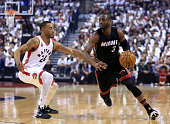 Dwyane Wade of the Miami Heat dribbles the ball as Norman Powell of the Toronto Raptors defends in the first half of Game One of the Eastern...