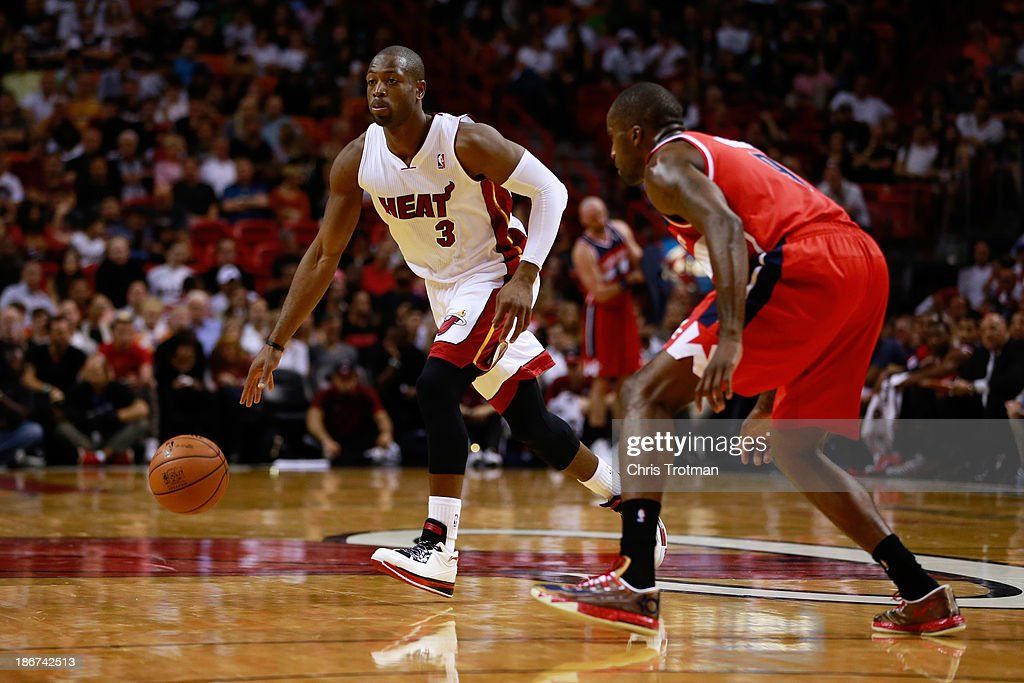 Dwyane Wade #3 of the Miami Heat dribbles the ball while guarded by Martell Webster #9 of the Washington Wizards at American Airlines Arena on November 3, 2013 in Miami, Florida.