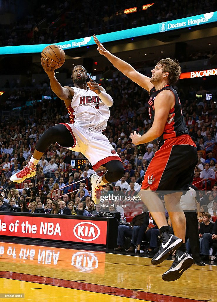 Dwyane Wade of the Miami Heat drives against Aaron Gray of the Toronto Raptors during a game at American Airlines Arena on January 23 2013 in Miami...