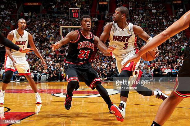 Dwyane Wade of the Miami Heat drives against Jimmy Butler of the Chicago Bulls on January 4 2013 at American Airlines Arena in Miami Florida NOTE TO...