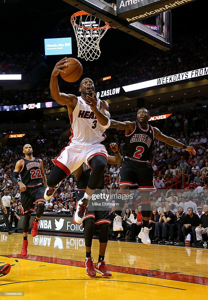 Dwyane Wade #3 of the Miami Heat drives past Nate Robinson #2 of the Chicago Bulls during a game at AmericanAirlines Arena on January 4, 2013 in Miami, Florida.